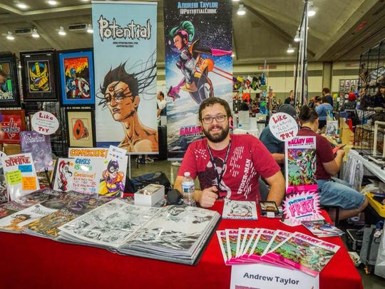 """Andrew Taylor sits at a booth promoting the """"Potential"""" comic book series and his other works at the Baltimore Comic Con in 2016."""