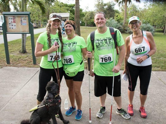 Sandy Godfrey, second from left, placed first in her age group at the annual Sprint for Sight 5K run/walk at Gleason Park. She lost her sight in her 30s.
