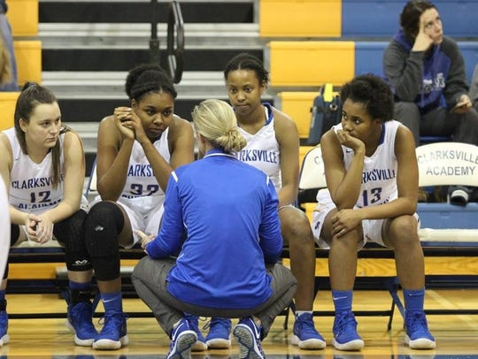 Clarksville Academy coach Carrie Daniels kneels to