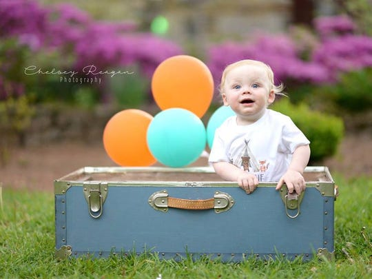 Landen's baby session included a cute suitcase and balloons set in front of beautiful azaleas in the background.