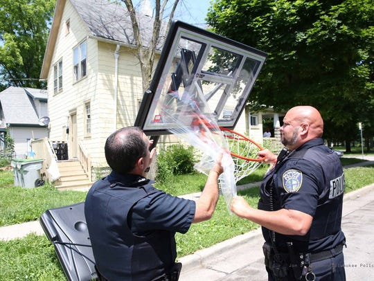 Milwaukee Police oficers install a new basketball hoop