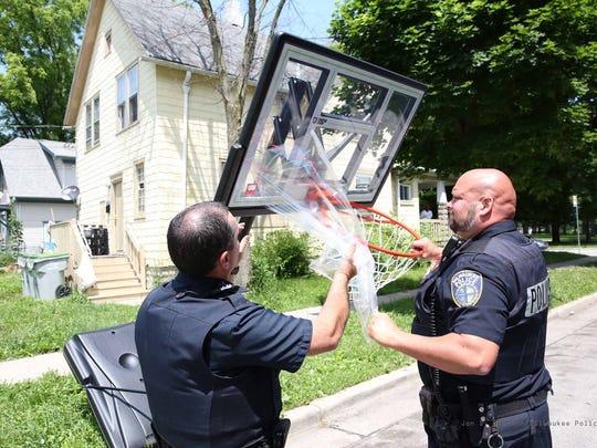Milwaukee Police oficers install a new basketball hoop