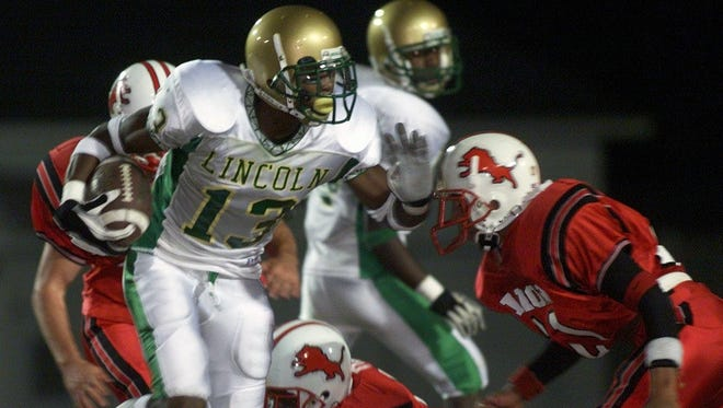 The Leon-Lincoln rivalry has been strong since its inception in 1977. Here, Lincoln receiver Antonio Cromartie, now an All-Pro NFL cornerback, runs for a first down against would-be Leon tacklers.