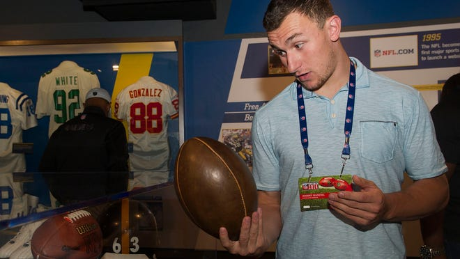 Cleveland Browns rookie Johnny Manziel looks at the size of a replica of a 1906 football, during the 2014 NFL Rookie Symposium at the Pro Football Hall of Fame in Canton, Ohio, Saturday, June 28, 2014.