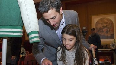 """Actor Josh Saviano shows his daughter Noa, 7, Polaroid photographs from the award-winning TV series: """"The Wonder Years"""" during a ceremony to donate show memorabilia to the Smithsonian's National Museum of American History in Washington,  Tuesday. Savanna played Paul Pfeifer in the show which aired  from 1988-1993 and depicted the everyday life of a boy growing up in an American suburb during the late 1960's and early 1970's."""