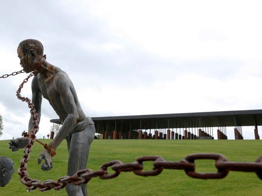 A statue of a chained man is on display at the National Memorial for Peace and Justice, a new memorial to honor thousands of people killed in racist lynchings, Sunday, April 22, 2018, in Montgomery, Ala. The national memorial aims to teach about America's past in hope of promoting understanding and healing. It's scheduled to open on Thursday. (AP Photo/Brynn Anderson)