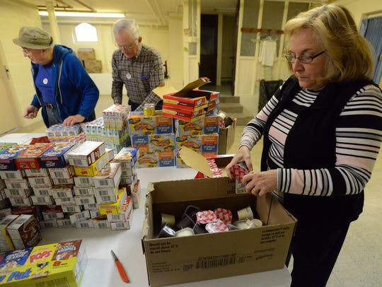 Sue Henwood, right, breaks apart packages of pudding