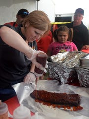 Sabrina Knapp of Bubba-Q's pours barbecue sauce on