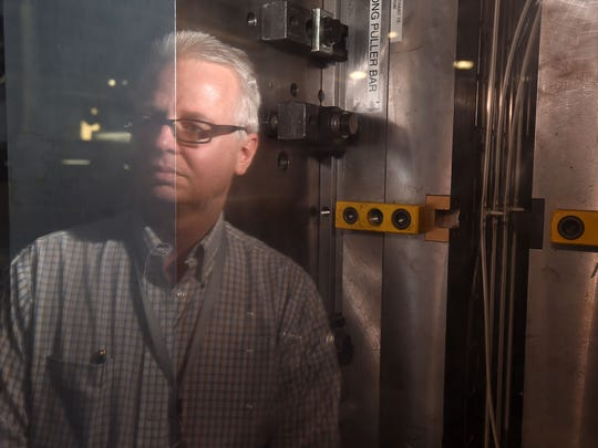 Micro Plastics Inc. President Tom Hill watches as an extruder machine produces plastic handcuffs at the company's Flippin plant. The initial response from the law enforcement community to the one-use plastic restraint has been positive.