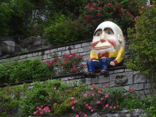 A Humpty Dumpty-like figure sits on a wall above downtown Eureka Springs. The 28th annual May Festival of the Arts is underway in Eureka Springs.