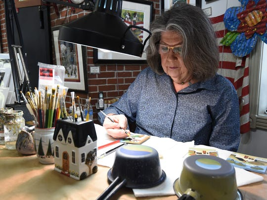 Sylvia Wilson works on a painting in her Wilson & Wilson Folk Art Co., located in the famous Flatiron building in Eureka Springs on Wednesday. The 28th annual May Festival of the Arts is underway in Eureka Springs.