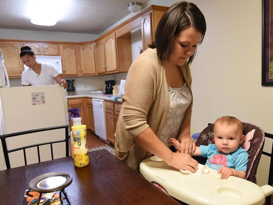 Sarah Reynolds cleans her niece's tray while partner Nikki Mitchell prepares lunch at the couple's duplex.