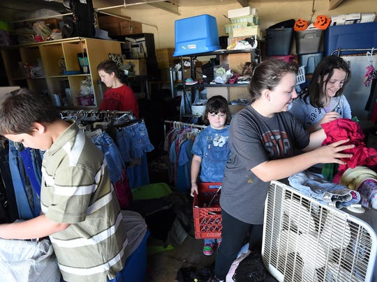From left, Brett Templin, 12, Chase Templin, 14, Aubrey Templin, 7, Heidi Templin, 16, and Andrea Templin, 13, work at the Christian Clothing Exchange on Thursday. The children's parents are disabled and live on a tight budget. Despite that, the family makes it a point to give back by volunteering.