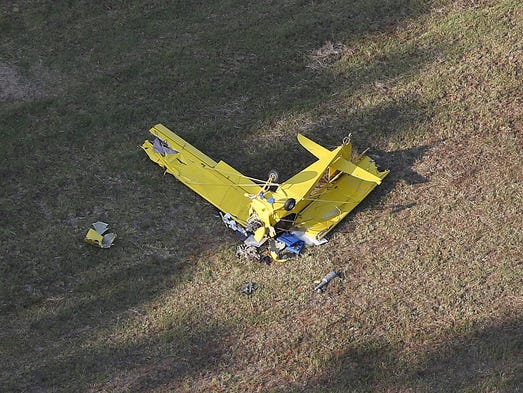 Officials investigate the wreckage of a single -engine aircraft in Clermont County's Tate Township near Bethel, Ohio Tuesday August 19, 2014. One man was transported to the Univeristy of Cincinnati Medical Center via AirCare, with non-life threatening injuries, according to Ohio State Patrol.