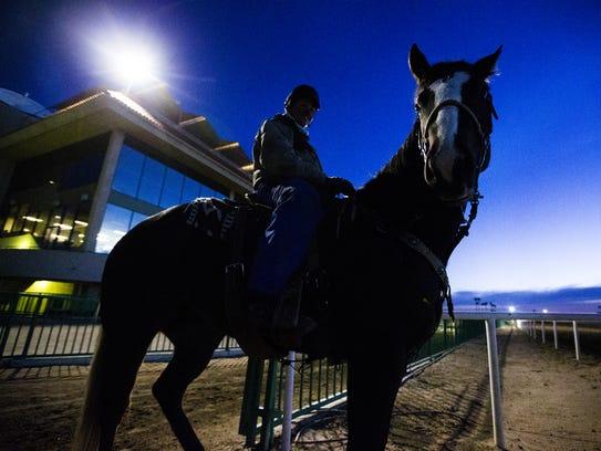 An outrider watches jockeys train at Turf Paradise