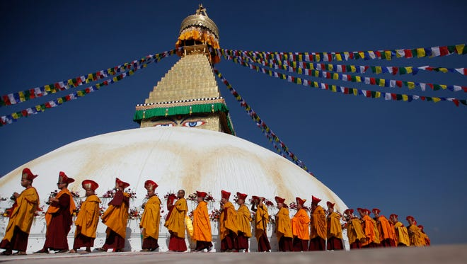 FILE- In this Nov. 20, 2016 file photo, Buddhist monks circle around the Boudhanath Stupa during during the final day of its purification ceremony in Kathmandu, Nepal. A year and a half after a colossal earthquake destroyed hundreds of its treasured historic sites, Nepal on Tuesday celebrated the restoration of the iconic Buddhist monument topped in gold that towers above Kathmandu.