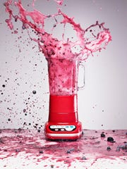 Berry juice splashing from blender