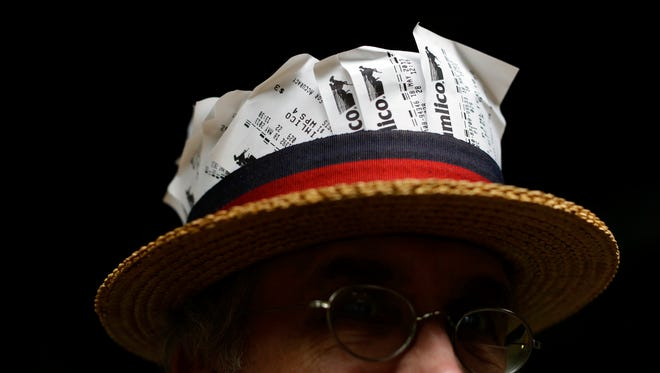 Spectator John Howard carries betting tickets in his straw hat at Pimlico Race Course in Baltimore, Saturday, May 18, 2013, before the 138th running of the Preakness Stakes horse race.