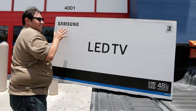 In this Monday, May 22, 2017, photo, Edward Calixto places a purchased LED TV in the back of his pickup truck, in Hialeah, Fla. On Thursday, Aug. 31, 2017, the Commerce Department issues its July report on consumer spending, which accounts for roughly 70 percent of U.S. economic activity.