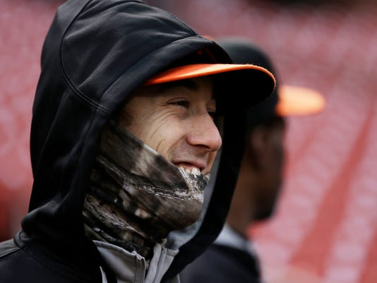 San Francisco Giants' Tim Lincecum covers up as it starts to rain during batting practice before Game 2 of the National League baseball championship series against the St. Louis Cardinals Sunday, Oct. 12, 2014, in St. Louis. (AP Photo/Jeff Roberson)