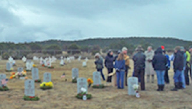 Volunteers get assignments as they lay wreaths on veterans' graves at the cemetery at Fort Stanton Saturday as part of the Wreaths Across America program. The group said 348 wreaths were laid at Fort Stanton and at the Forest Lawn cemetery in Ruidoso.