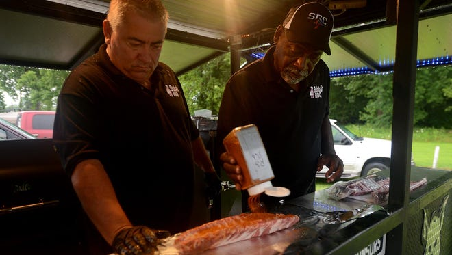 Billy Hill and Milton Phillips of Bubba's BBQ prepare a whole rack of ribs to be in the barbecue contest at the first annual Riders and Rockabilly Rally on Friday afternoon.
