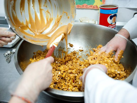 Melissa Morgan, left, and Aaron Rosenlund pour melted peanut butter and honey into cornflakes, oats and cranberries to make Peanut Butter Cranberry Bars at the Vermont Works for Women Fresh Food kitchen in Winooski on May 15.