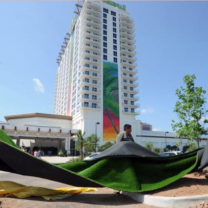Landscape workers install artificial turf in the parking area of Margaritaville as patrons were invited into the casino for it's soft opening June 13.