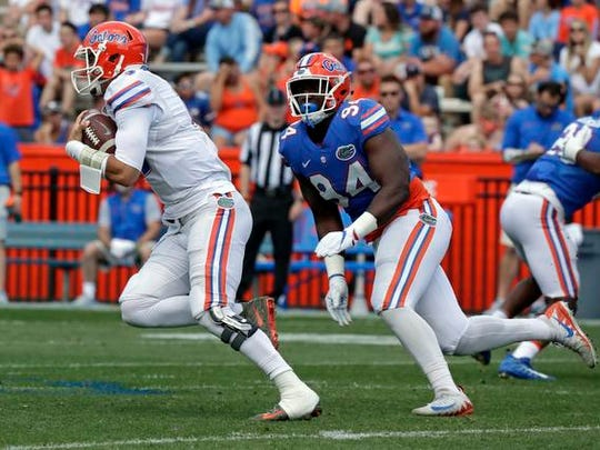Florida quarterback Feleipe Franks, left, takes off on a long run past defensive end Zachary Carter for a touchdown during an NCAA spring college football intrasquad game, Saturday, April 14, 2018, in Gainesville, Fla. (AP Photo/John Raoux)