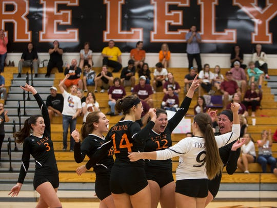 The Lely Trojans celebrate after scoring a point in the Class 5A regional semifinal volleyball match at Lely High School on Friday, Oct. 28, 2016.