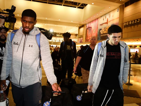 UCLA basketball players Cody Riley (left), LiAngelo Ball (right) and Jalen Hill (background center) are surrounded by the media as they leave the Los Angeles International Airport on Tuesday after returning home from China.