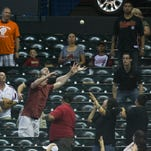 Fans try to grab a home run hit by Padres' Yasmani Grandal in the fifth inning against the Diamondbacks at Chase Field in Phoenix, AZ on Sunday, August 24, 2014.