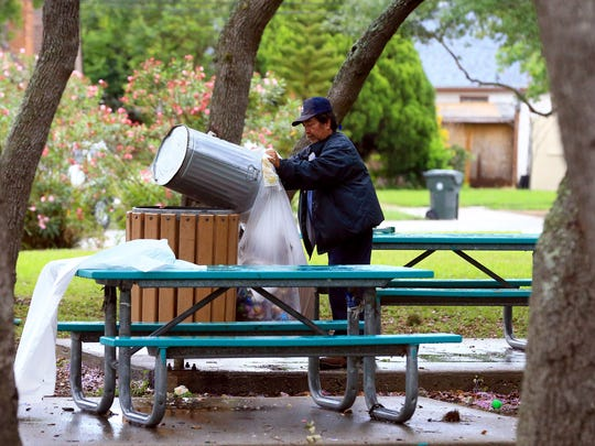 Park technician Rene Saenz from the Corpus Christi Parks & Recreation empties a trash can at Oak Park as crew members clean up after Easter on Monday, April 17, 2017, in Corpus Christi.