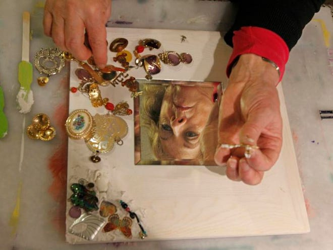 Linda Vinciguerra works on a mirror embellished with recycled items in her basement craft room.