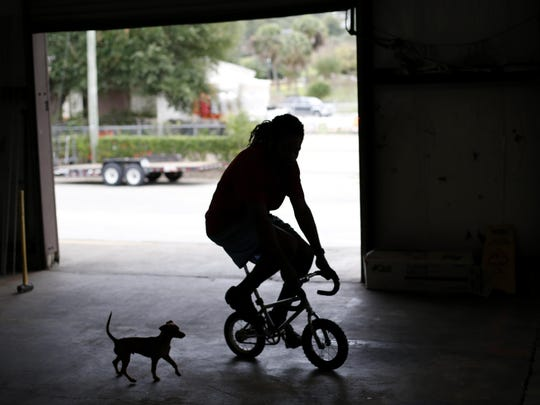 Head Mechanic Neely Williams rides a mini bike around the new warehouse location for Bicycle House Wednesday. The non-profit moved into the new space on FAMU Way at the end of this summer after leaving its original location which opened in 2010.