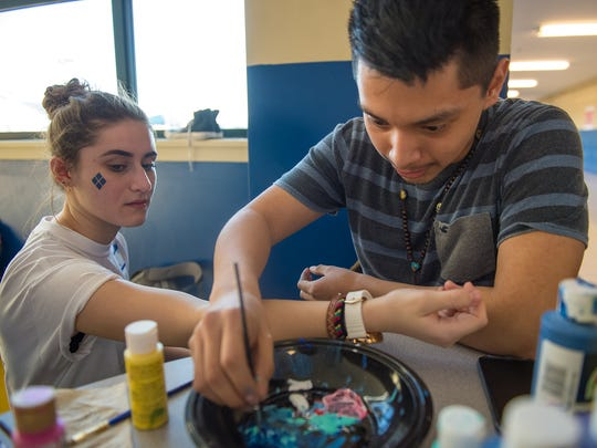 Cisco Batz dips a brush into paint as he draws on Katie Papoutsis, left, during Mini THON at Chambersburg Area Senior High School on Friday, Feb. 17, 2017 in Chambersburg, Pa.