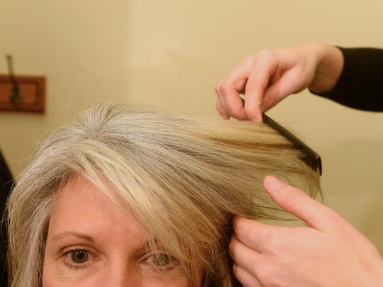 Carrie Reigis' hair was left a light blondish color after her stylist stripped her former brown color out. That allows her gray to grow in now with a stark stripe.