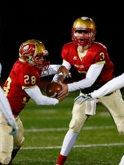 Mount Olive quarterback Liam Anderson hands off to Anthony DiJoseph during  NJSIAA North 1 Group IV opening-round game against Morris Knolls. November 10, 2017. Mount Olive, New Jersey