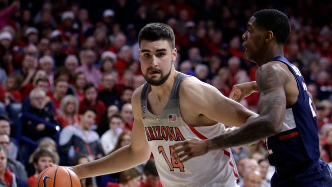 Dusan Ristic (14) drives on Connecticut guard Terry Larrier during the first half of Arizona's 73-58 win.