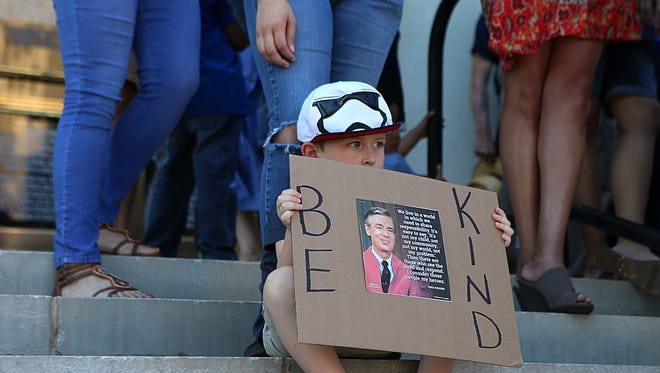 """A child holds up a """"Be Kind"""" sign with a photo of Mr. Rogers on the steps of the Tom Green County Courthouse during a prayer vigil for immigrant families being separated  Monday, June 25, 2018."""