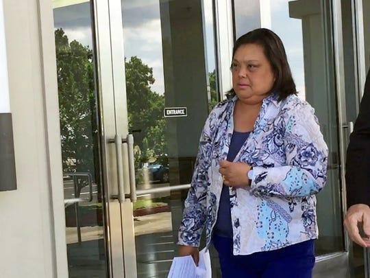 Lerma Aquino, left, leaves the District Court of Guam