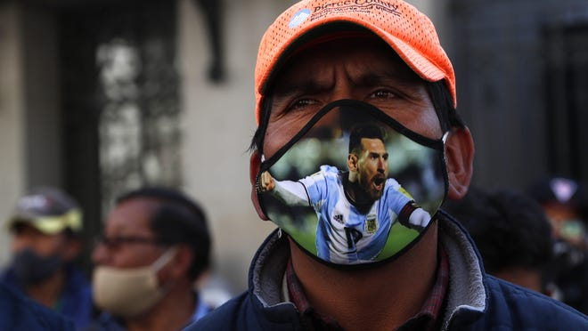 A public transport driver, wearing a protective face mask emblazoned with an image of Lionel Messi, attends a protest demanding an increase in fares because quarantine measures to curb the spread of the new coronavirus have decreased his income, in La Paz, Bolivia, Wednesday, July 1, 2020.
