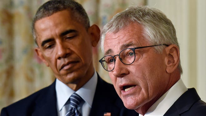 President Barack Obama, left, listens as Defense Secretary Chuck Hagel, right, talks about his resignation Nov. 24 in the White House in Washington. Hagel is stepping down under pressure from Obama's Cabinet, senior administration officials said Monday, following a tenure in which he has struggled to break through the White House's insular foreign policy team.