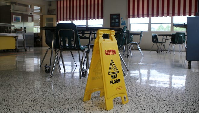 A wet floor sign is seen in the cafeteria at Parkview Learning Center on Tuesday. The cafeteria was one of the rooms that flooded, causing the school to be shut down for the day.