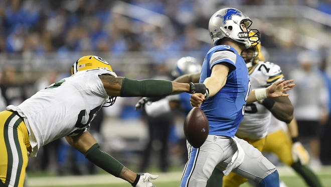 Green Bay Packers linebacker Julius Peppers (56) knocks the ball loose from Detroit Lions quarterback Matthew Stafford (9) at Ford Field. The Packers recovered the ball on the play.