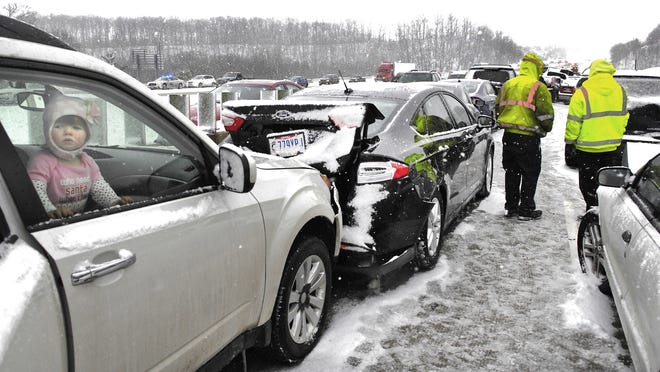 A young girl looks out of her car window as crews work to clear a massive pileup on Interstate 90 in Leroy Township, Ohio, on Dec. 24, 2013.