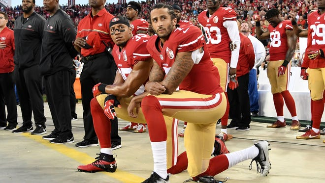 Colin Kaepernick and Eric Reid kneel during the national anthem prior to the 49ers' season opener.