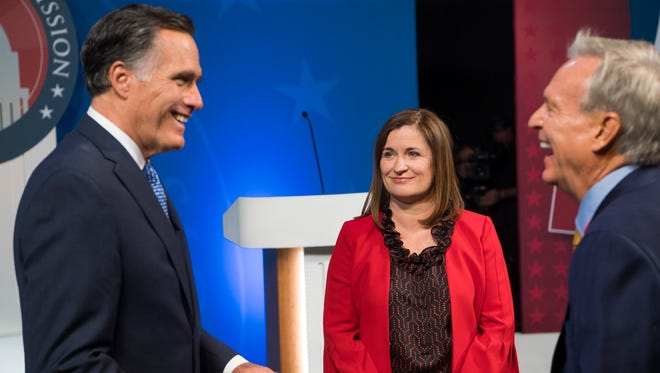 U.S. Senate candidates Mitt Romney (R) and Jenny Wilson (D) flip a coin before the debate at the America First Event Center in Cedar City Tuesday, October 9, 2018.