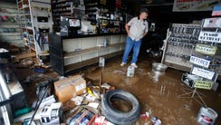 Paul Raines looks over his flooded Western Auto store