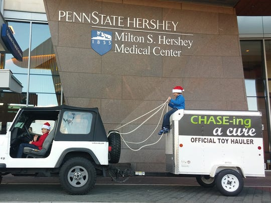Chase Kemberling sits on top of the family's new toy-hauling trailer while his brother, Travis Kemberling, is inside the Jeep. The Kemberling family started the charity, Chasing A Cure, to provide toys to young patients at Hershey Medical Center.